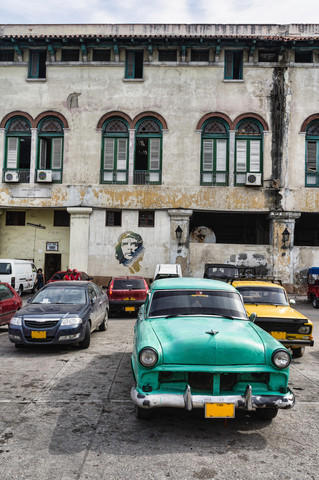 Picture of an old car in Havana with street art of Che Guevara on a building in the background