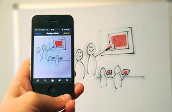 Smarttelefon i forgrunn, tek bilde av illustrasjon på tavle