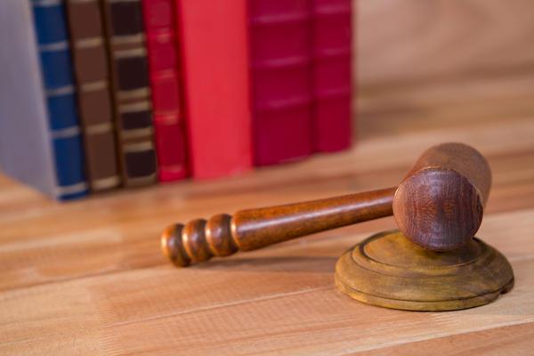 Bilde av en dommers hammer med bøker i bakgrunnen