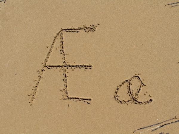 bokstaven Æ, liten og stor, skriven i sand