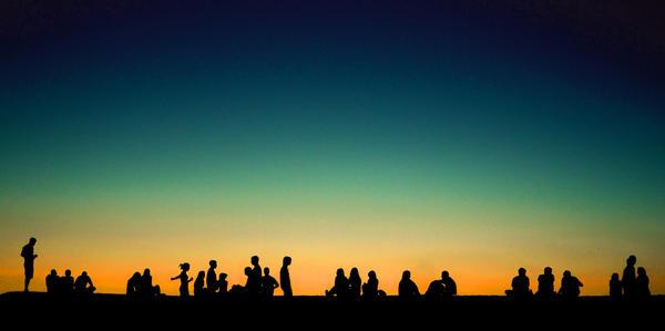 Siluetter av mange personer i en solnedgang