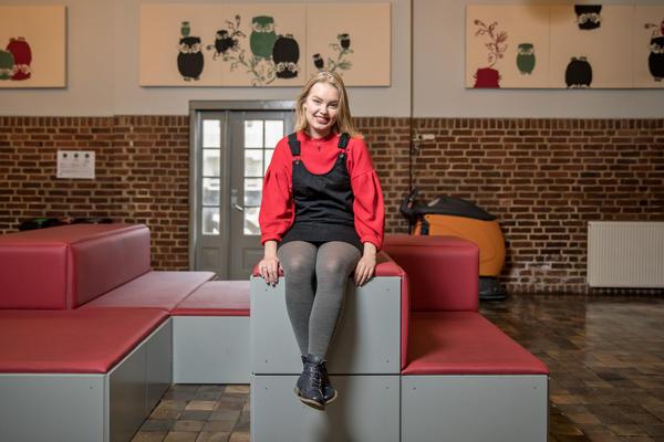 En kvinnelig lektorstudent sitter på en benk inne på Sydneshaugen skole