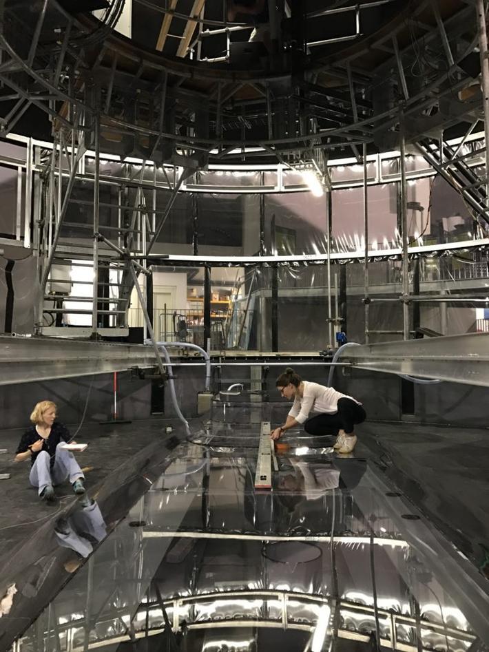 Elin Darelius og Nadine Steiger forbereder eksperimentene i den roterende tanken i Grenoble. Glassfjellet Nadine sitter på er Antarktis, mens Elin har satt seg på havbunnen utenfor.