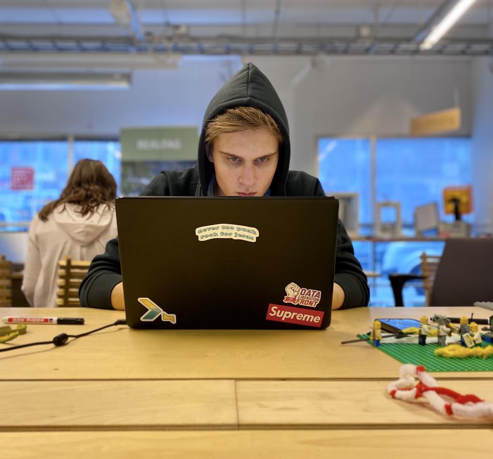 Student sitter konsentrert med pcen sin