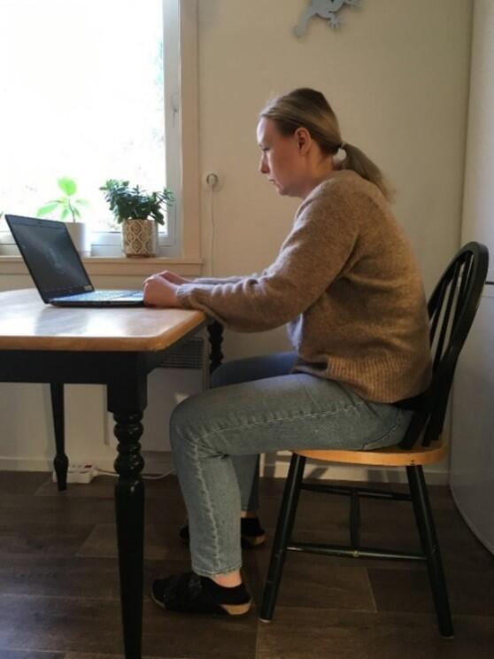 Kvinne sitter på stol med krum rygg og jobber på laptop på et kjøkkenbord.