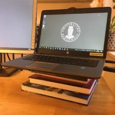 En laptopp oppå en stabel med bøker