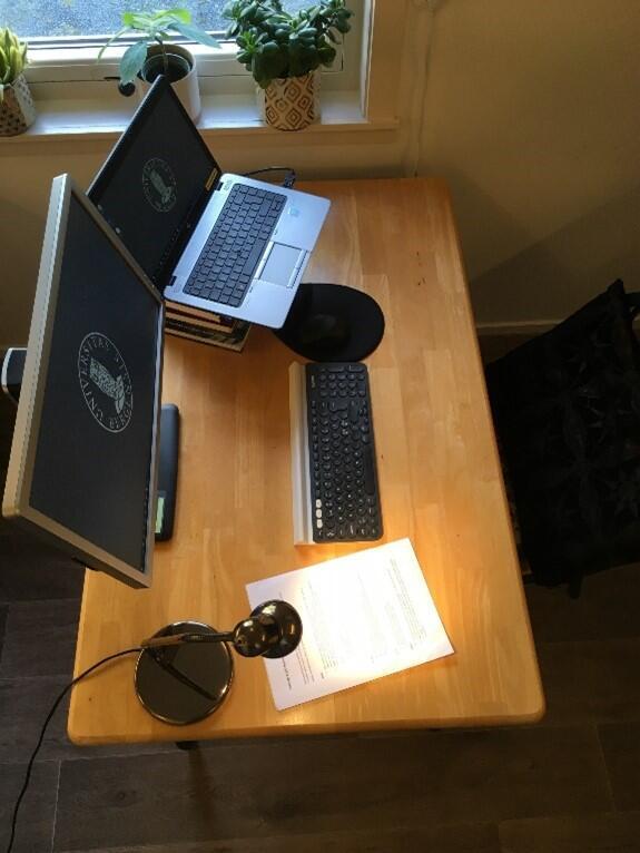 Pult med laptop, dataskjerm og arbeidslampe.