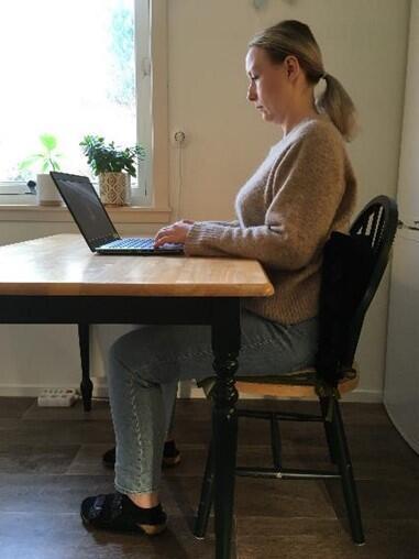 Kvinne sitter på stol med rett rygg og pute i korsryggen og jobber på laptop på et kjøkkenbord, men kroppen helt inntil bordet-..
