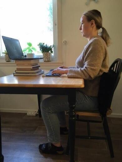Kvinne sitter på stol med rett rygg og pute i korsryggen og jobber på laptop på et kjøkkenbord, med kroppen helt inntil bordet. Hun har også støttet opp laptopen med flere bøker, slik at den kommer høyere.