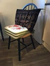 Kjøkkenstol med puter for å heve setet og for støtte i korsryggen.