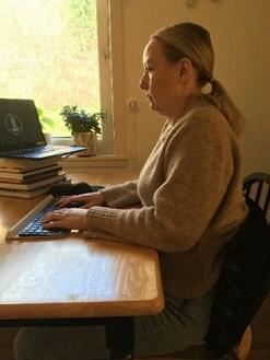 Kvinne sitter inntil pult med hendene på et tastatur og ser på laptop som står oppå en haug med bøker.