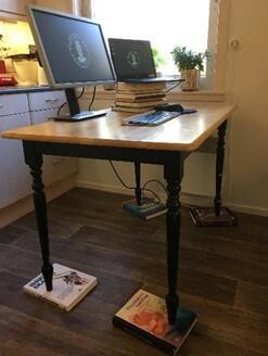 Bord med to dataskjermer (en vanlig og en laptop), som er høydejustert med bøker under bordbeina.