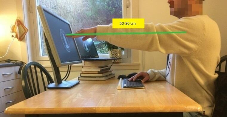 Man som viser en armlengdes avstand fra seg selv til PC-skjermen.
