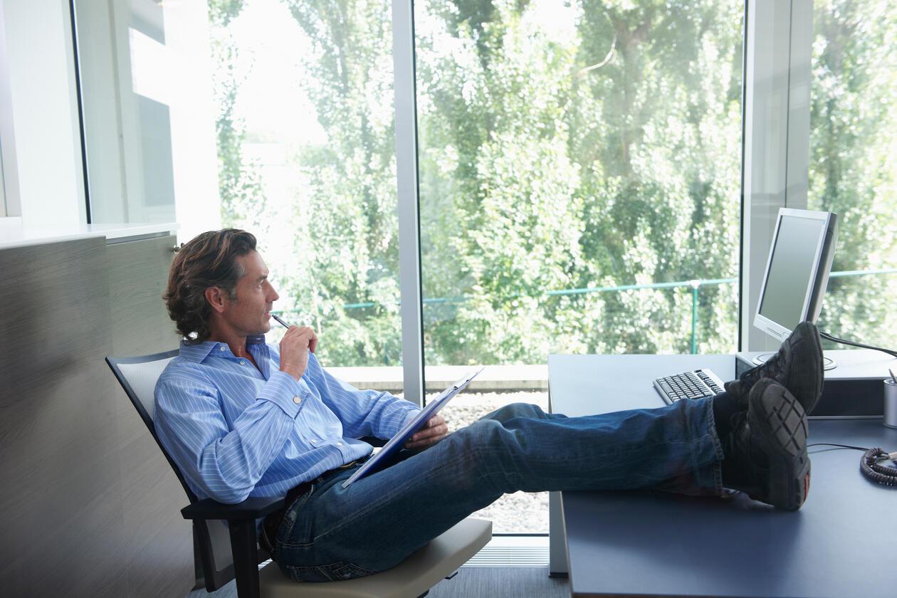 Mann med beina på pulten som ser tankelfull ut av vinduet. Utenfor vinduet er det grønne trær.