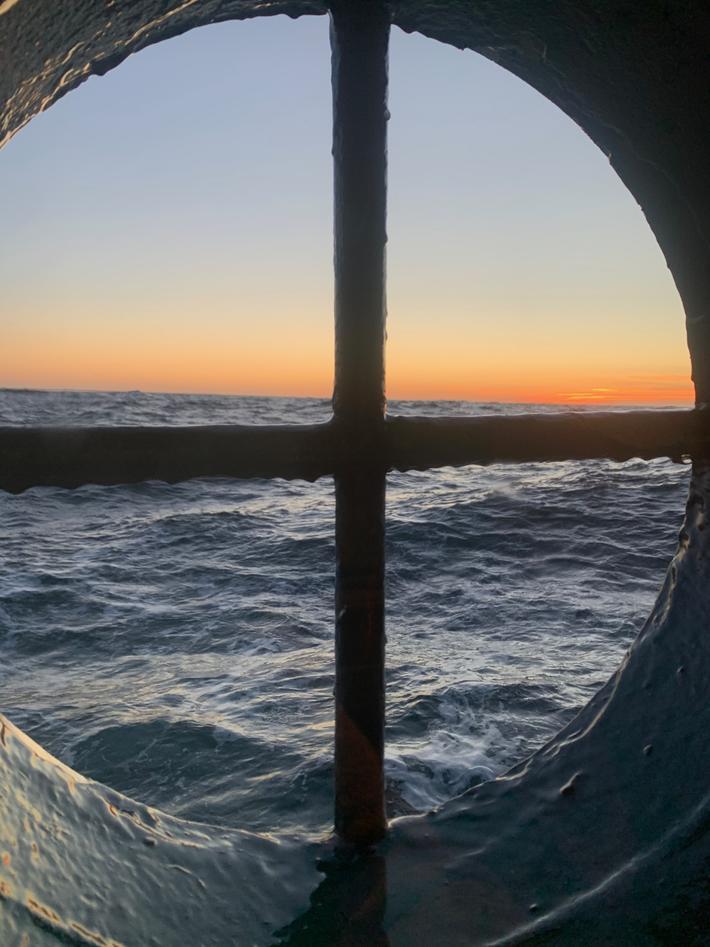 Solnedgang sett fra vindu på båt