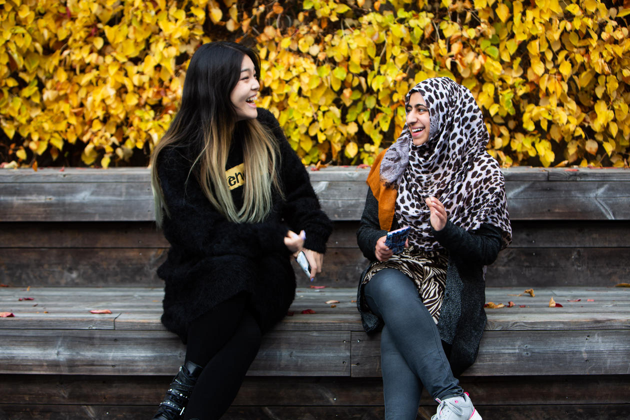 To elever på en benk som ser på hverandre og smiler.