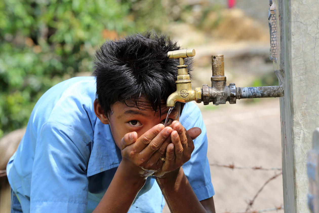 Boy drinks water from a tap stand at the school, NEWAH WASH water project in Puware Shikhar, Udayapur District, Nepal.