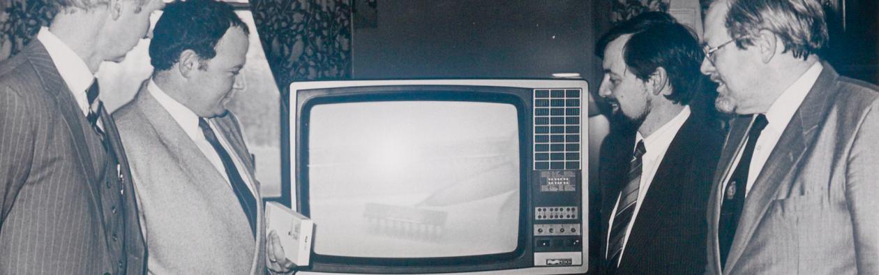 Fire menn ser på eit fjernsyn med undervisingsmateriale på video.