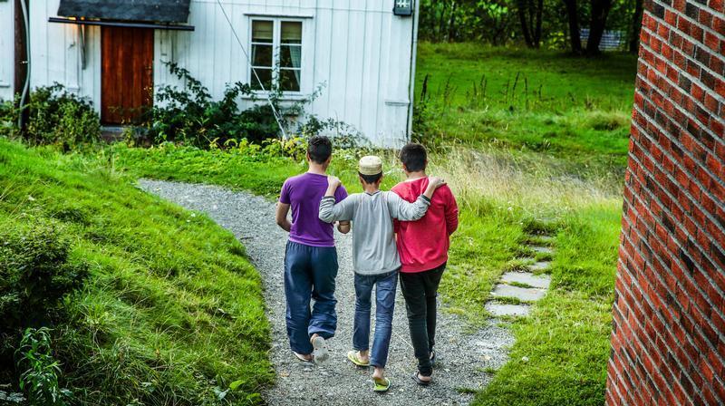 Tre barn med ryggen til