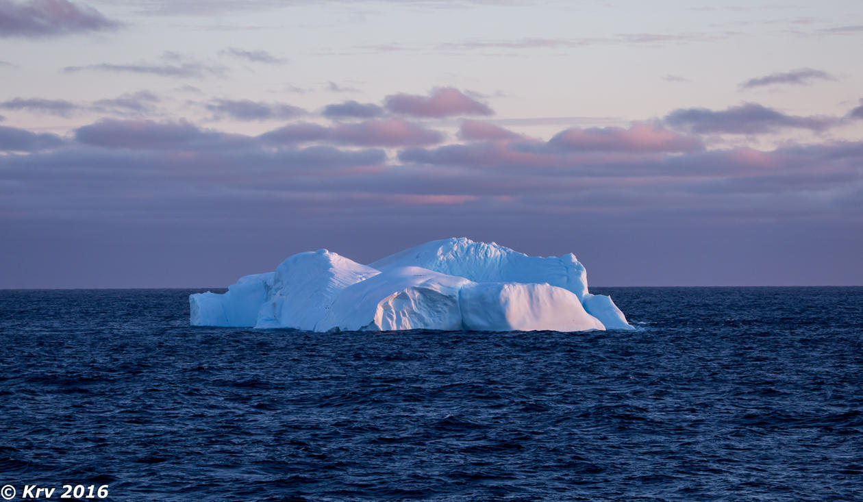 An iceberg floating in the blue ocean