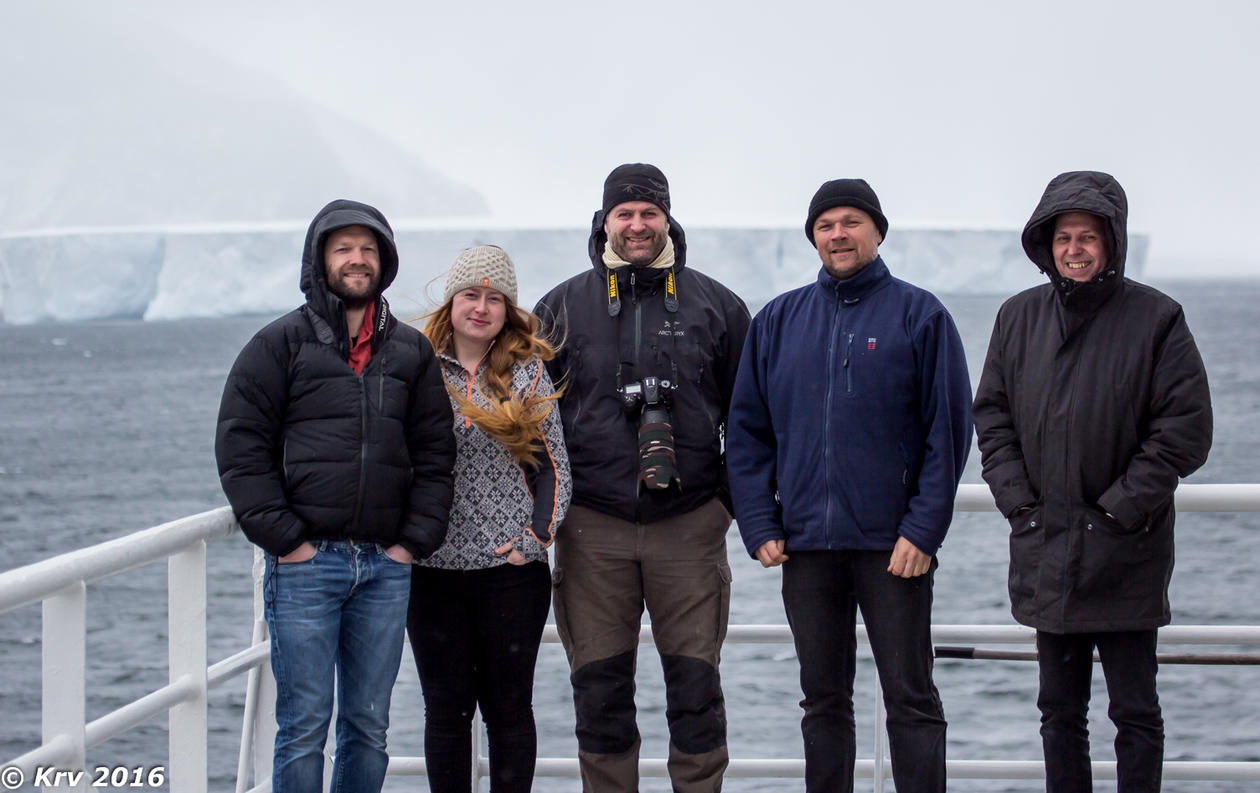 A group of people standing on deck of a vessel, with arctic background