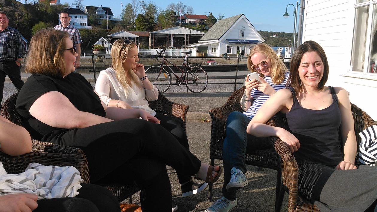Four ladies enjoying sun, mobile phone, and discussions.