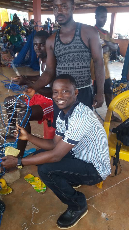 Fishermen mending their net.