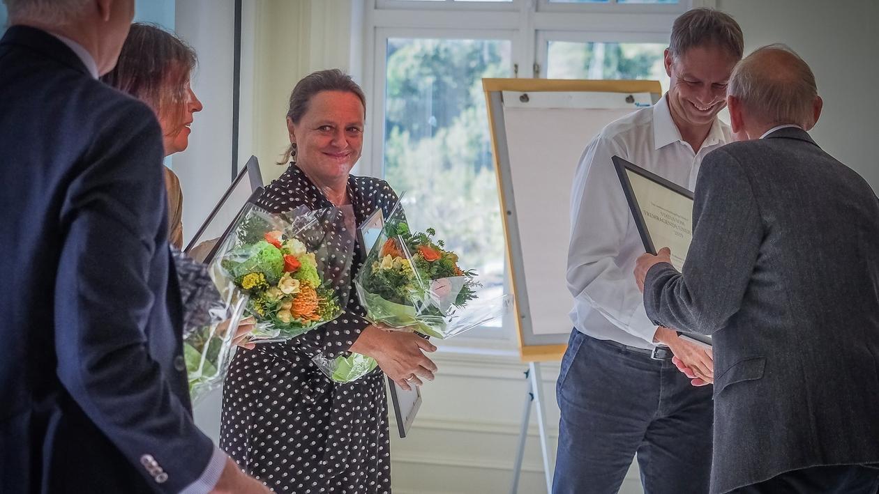 De fire meritterte underviserne mottar diplom og blomster fra dekanen.