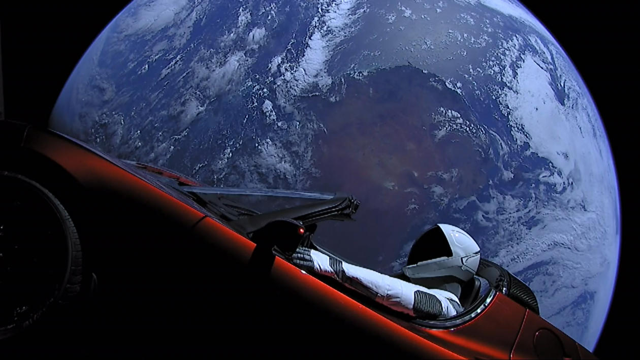 "Elon Musk's Tesla Roadster, with Earth in background. ""Spaceman"" mannequin wearing SpaceX Spacesuit in driving seat"