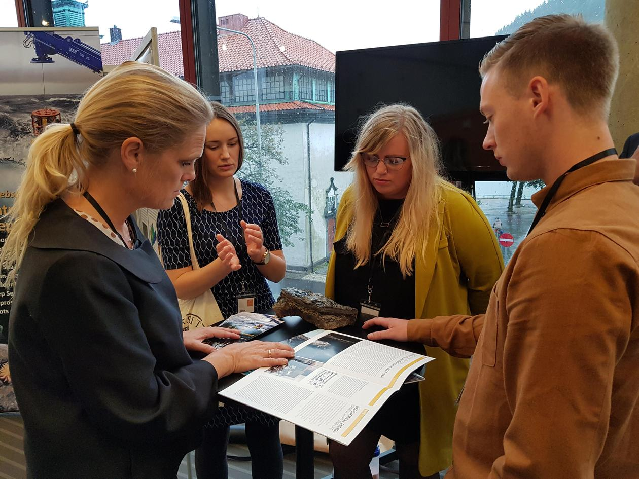 Linn Merethe Olsen explaining some of the detailed work that has been done at the K. G. Jebsen Deep Sea Centre throughout the year. Marine mineral sample taken by UiB and the annual report.