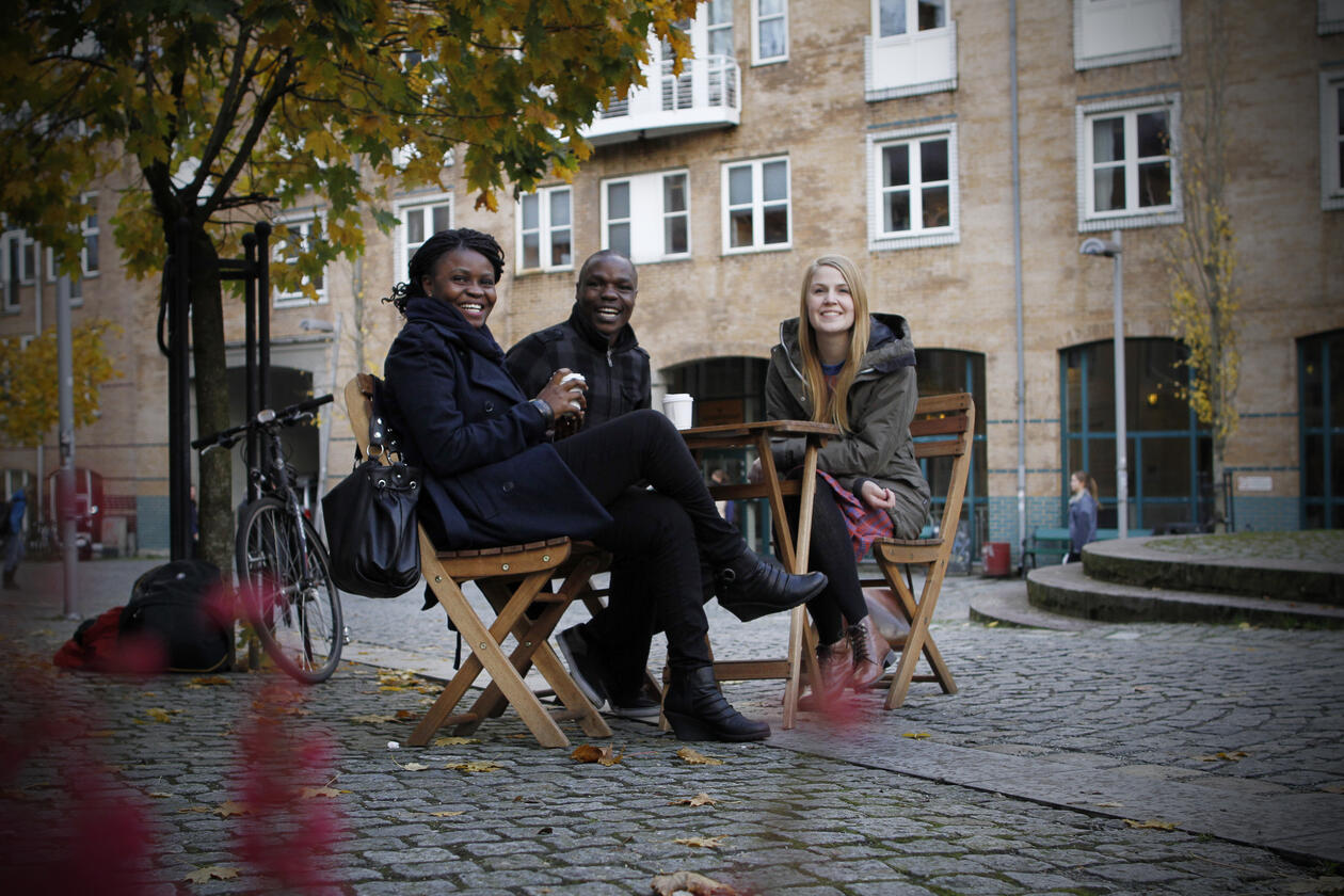 Three students sitting around a coffee table outside the Faculty of Social Science