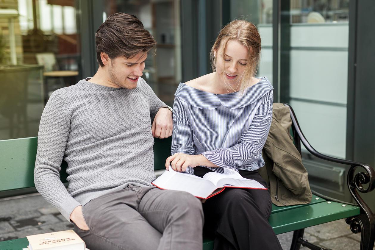 To studenter på en benk leser i en lovbok