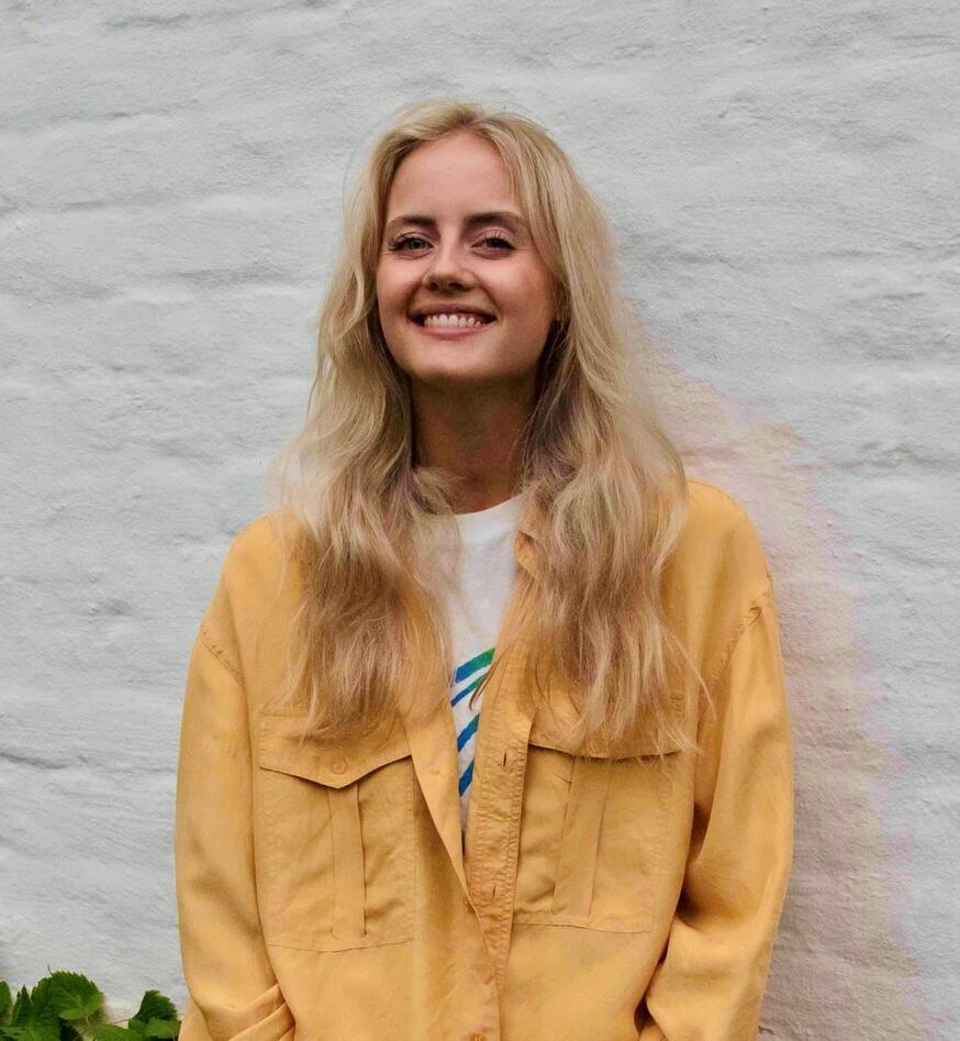 Portrett av Kristin Haukaas Myhre, smilende med blond hår, gul jakke mot en hvit vegg