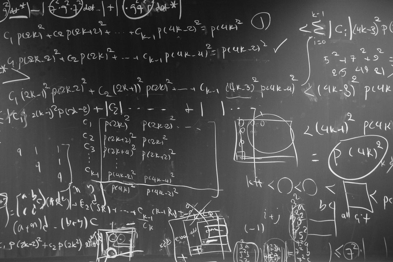 Image of blackboard with algorithms written all over it.