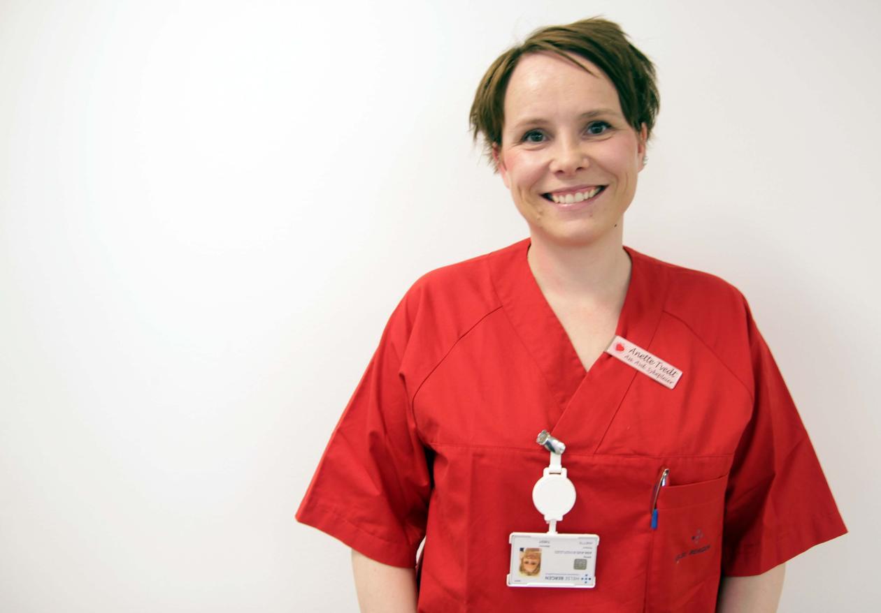 SIGNALRØD: Den røde uniformen som Anette Tvedt bruker ved Mottaksklinikken på Haukeland i dag skal symbolisere energi, aktivitet og handling. Det er funksjon fremfor tilhørighet og gruppe som er i fokus på uniformene i dag. Slik har det ikke alltid vært.