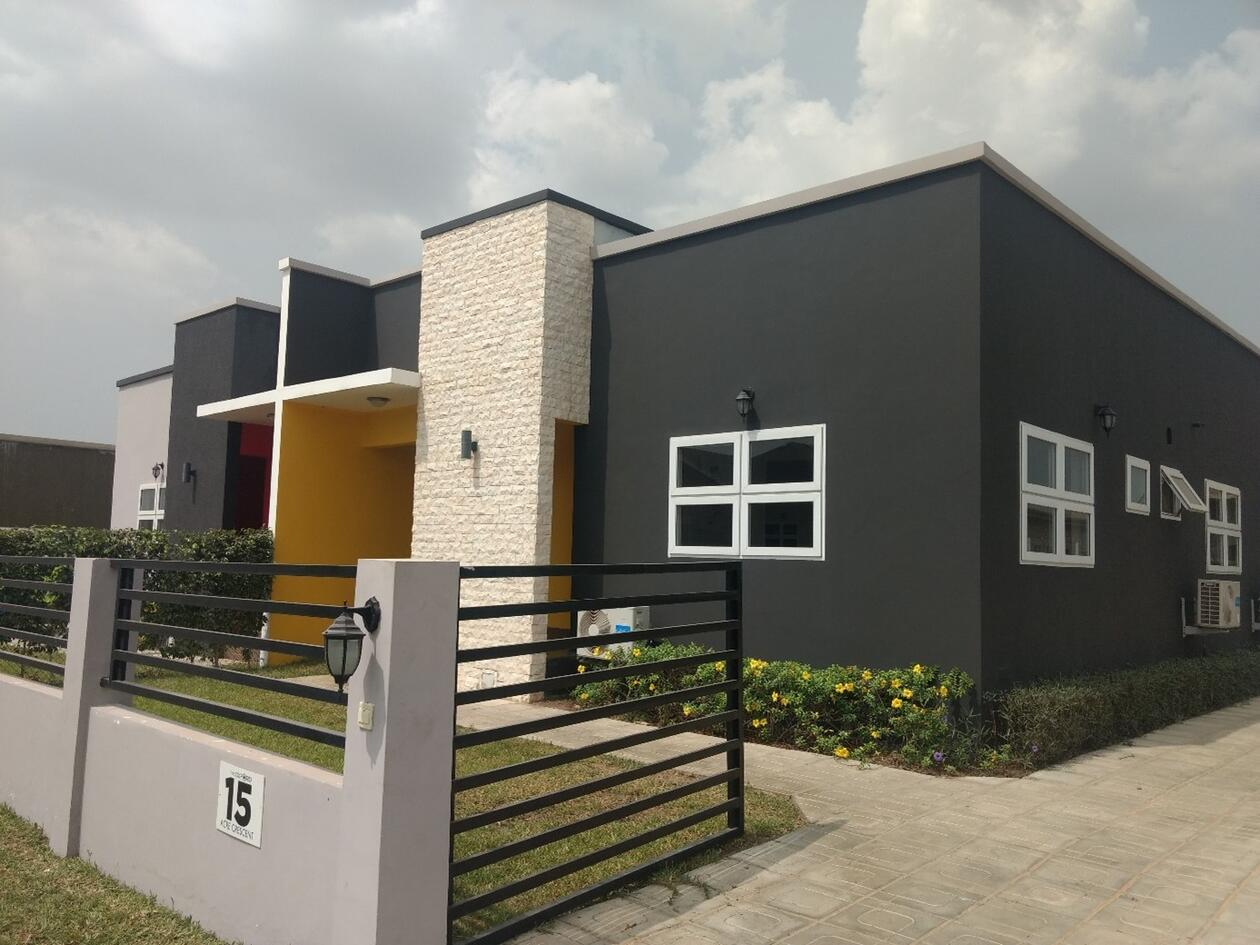 Image of one of the newly built houses in Appolonia. It is in a modern style, with grey walls and a yellow accent around the doorway. There is a small garden in front of the house, surrounded by a low fence.