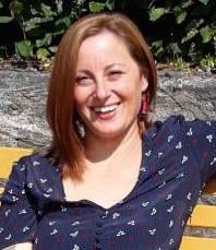 Bilde av Aristea Fotopoulou, kvinne med skulderlangt hår smiler.