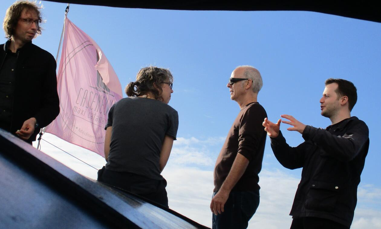 Four people next to each other, with blue skies and a pink flag in the background