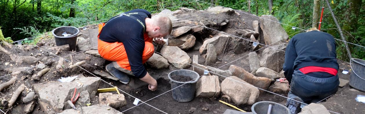 Arkeologar sit i ein steinhaug rekonstrurer ei grav