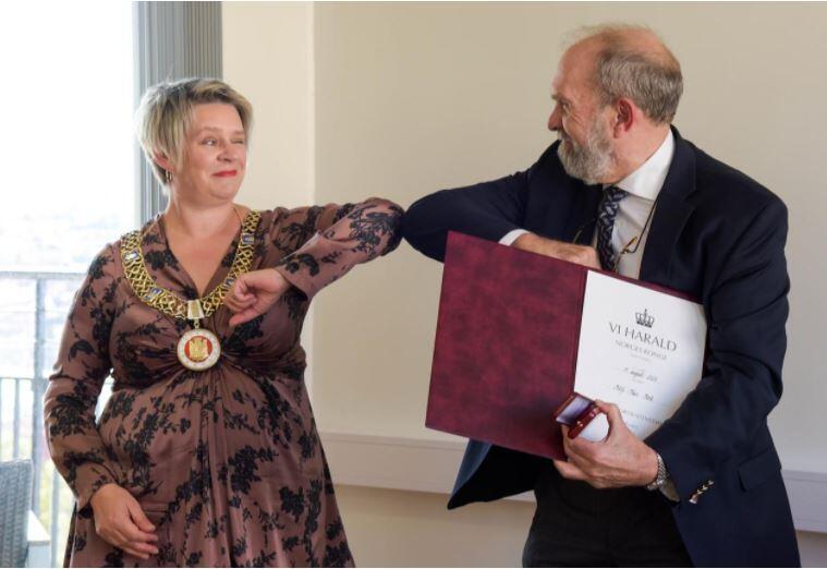 Ordfører Marte Mjøs Pedersen gir Rolf Reed en koronavennleg albuehilsen etter utdelinga av fortenestemedaljen