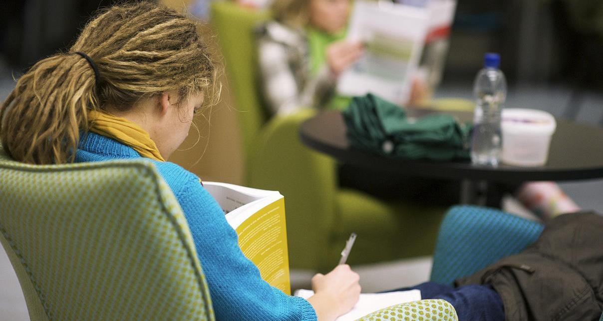 En jente leser i en bok i en stol på biblioteket
