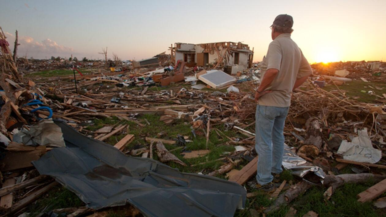 Man looks at damage caused by tornado