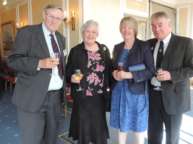 John and Hilary Birks, Dawn and Des Thompson standing together each with a celebratory drink