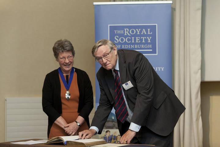 Jocelyn Bell Burnell invites John Birks to sign the Fellows book of the Royal Society of Edinburgh