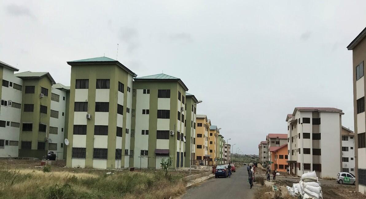 Several newly built appartment complexes, alle with a green decorative stripe on the front. There is a one lane road to the right, with more buildings on the other side.