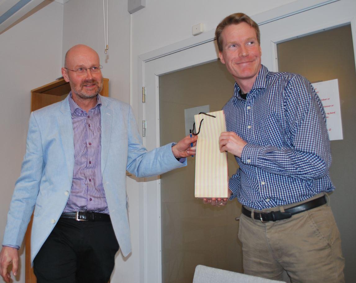 Instituttleder Jan Heiret, t.v., overrekker en vinflaske til Eivind Heldaas Seland, som oppnådde flest publikasjonspoeng av instituttets forskere i 2016.