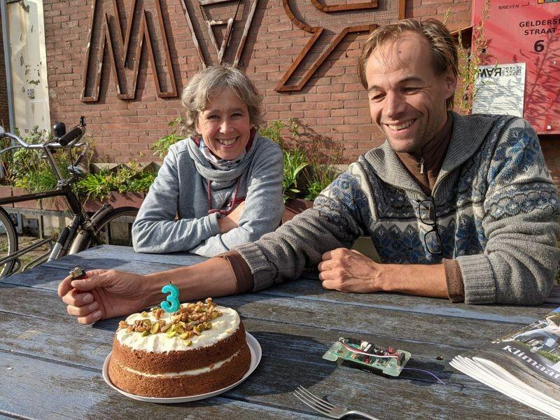 A woman, a man and a cake with a candle shaped as the number 3