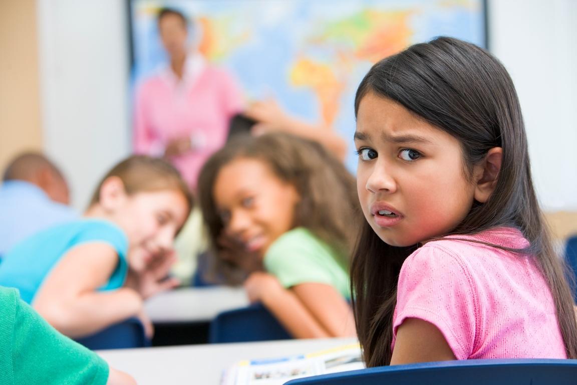 Barn i klasserom som blir baksnakket av  medelever