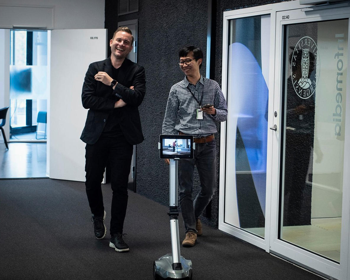 Media Futures christoff Trattner spaserer i gangen med robot