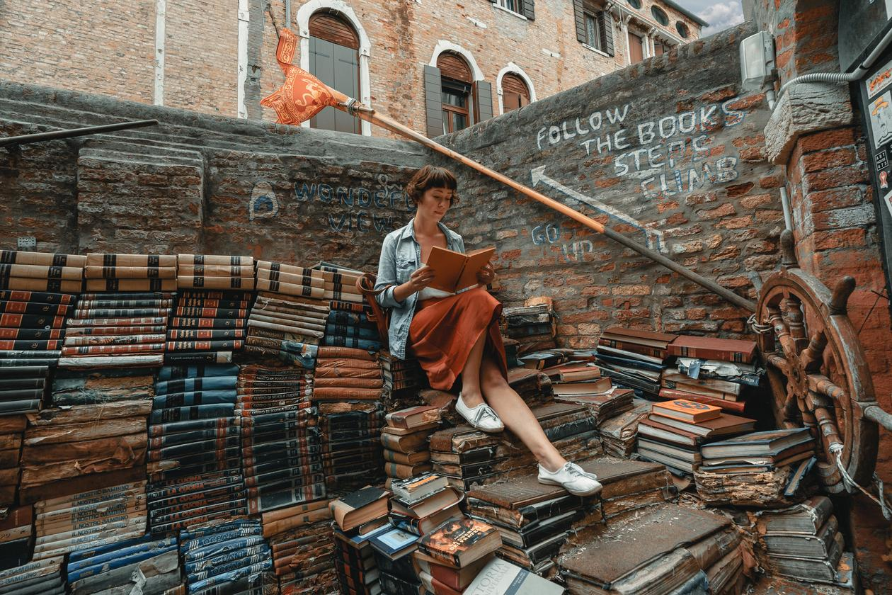 Woman sitting on a books and reading a book